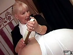 Mature blonde mistress orders enslaved man to suck huge black strap on to make it wet for his ass.